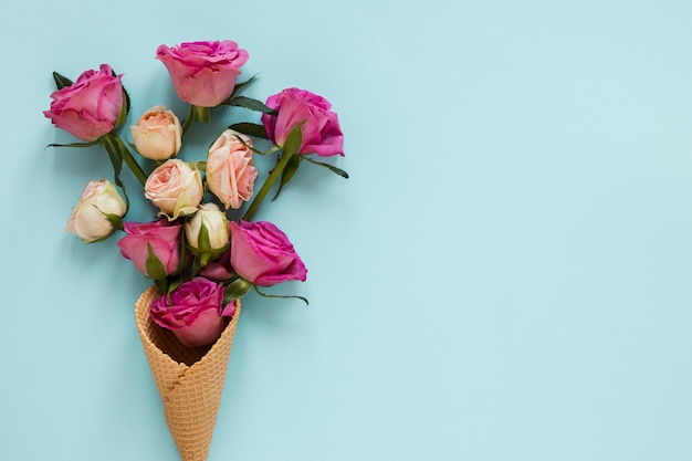 Bouquet of roses wrapped in ice cream cone with copy space background