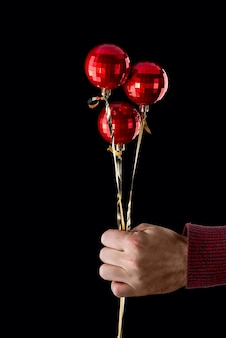Bouquet of shiny christmas balls in a man's hand