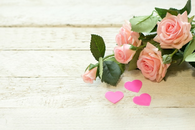 Bouquet of small pink roses lying on white textured table with hearts background