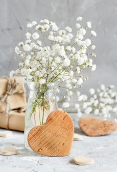 Bouquet of small white flowers and wooden hearts on a grey background