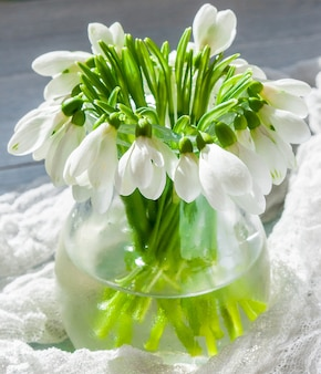 木製の背景とカラーランナーの花束スノードロップ。春の花。母の日、バレンタインデー、女性の日。ウェディングブーケ。コピースペース。