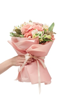 Bouquet of  soft pink flowers in pink wrapping paper in woman hands isolated on white surface