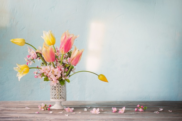 Bouquet of spring flowers on blue wall