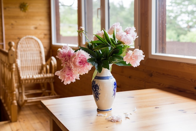 A bouquet of spring peonies in a vase on a table on a cozy terrace.