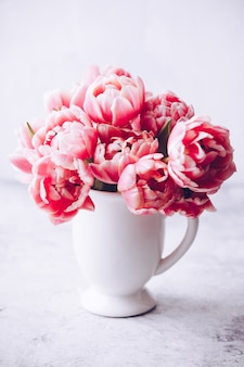 Bouquet of spring tulips in vase on shabby chic background
