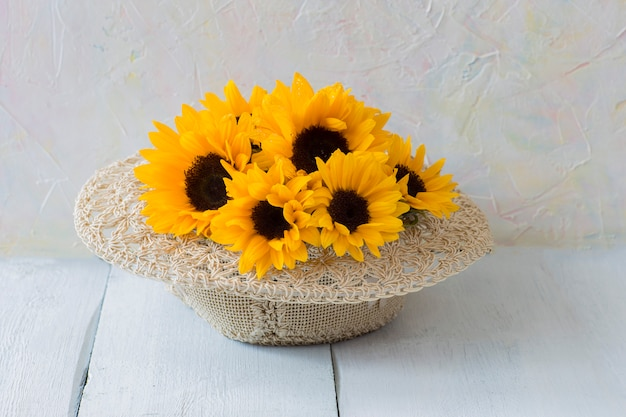 Bouquet of sunflowers in a straw hat on a white wooden table