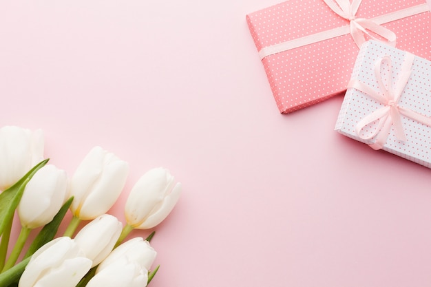 Bouquet of tulip flowers and gifts on pink background