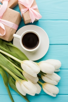 Bouquet of tulip flowers with cup of coffee and gifts
