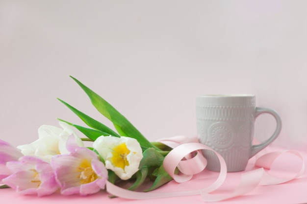 Bouquet of tulips and a coffee cup on a pink pastel background.