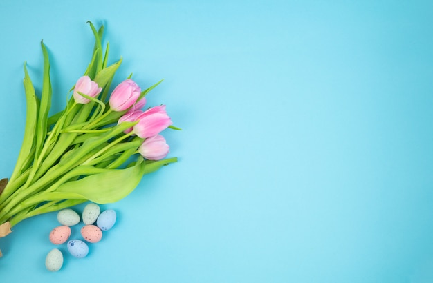 Bouquet of tulips and easter eggs on a blue background. copy space.