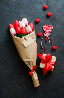 Bouquet of tulips and gift box on dark background.