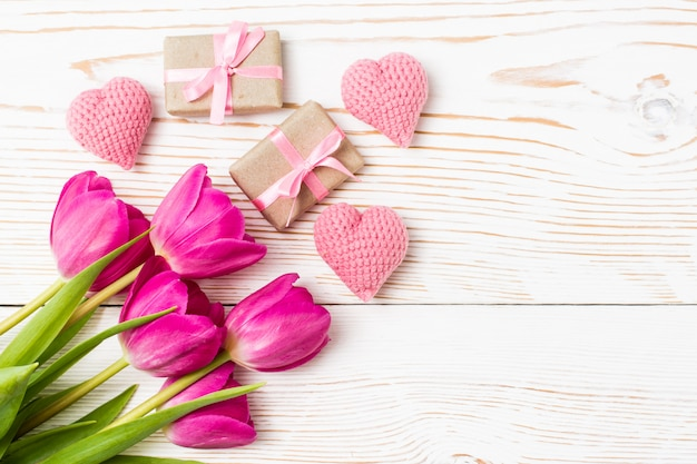 Bouquet of tulips, gifts and hearts on a white wood, top view