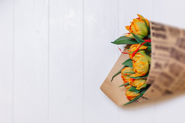 Bouquet of tulips in paper on white background