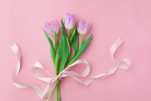 Bouquet of tulips on a pink pastel background.