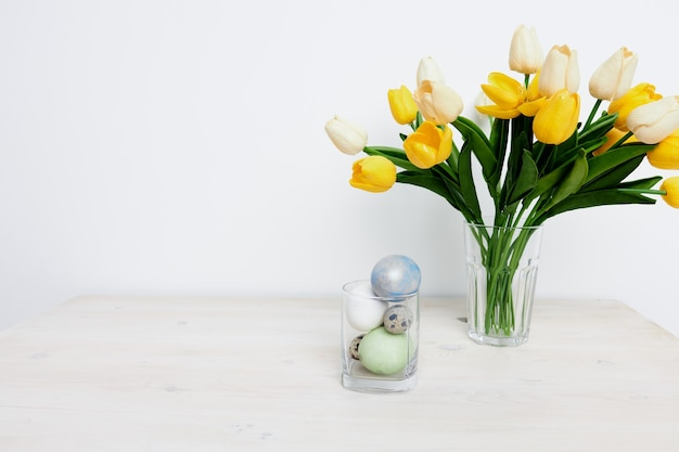 A bouquet of tulips on the table and easter eggs in a glass
