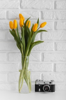 Bouquet of tulips in transparent vase with camera