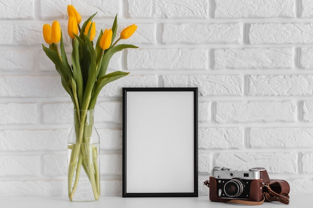 Bouquet of tulips in transparent vase with empty frame and camera