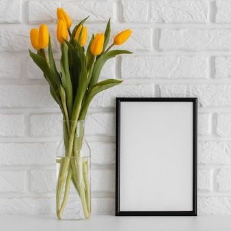 Bouquet of tulips in transparent vase with empty frame