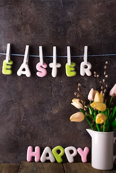 Bouquet of tulips in a vase and letters happy easter on clothespins on a concrete background