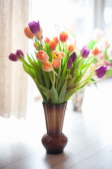 Bouquet tulips on the window in a vase