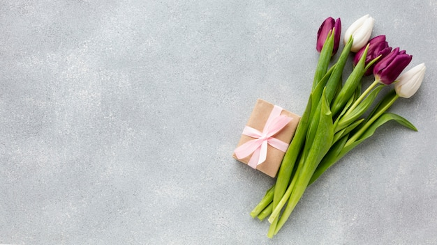 Bouquet of tulips with wrapped gift and copy space