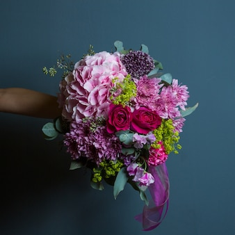 A bouquet of variety of flowers with rich colors and leaves in the hands of a bride on wall