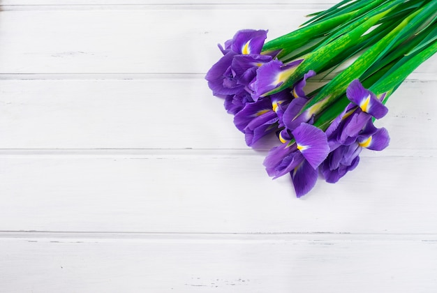 Bouquet of violet iris on wooden white background. present for valentine's day.