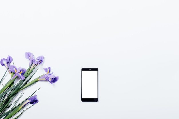 Bouquet of violet irises and mobile phone on white table top view