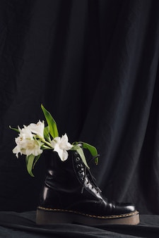 Bouquet of white blooms with green leaves in dark boot