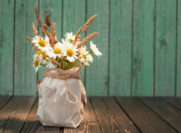 Bouquet of white chamomile flowers with dry ears in a kraft paper vase on a shabby wooden background in a rustic style