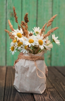Bouquet of white chamomile flowers with dry ears in a kraft paper vase