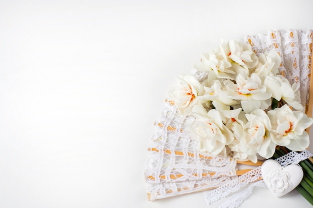 A bouquet of white daffodils, lace fan and heart
