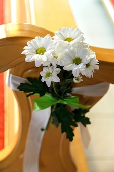 A bouquet of white daisies is tied to the back of a chair