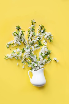 Bouquet white flowers blooming cherry fruit tree in vase on yellow.  flat lay.