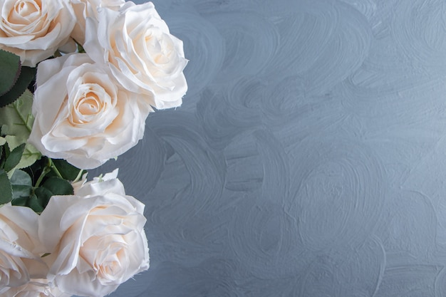 A bouquet of white flowers in a bucket, on the white table.