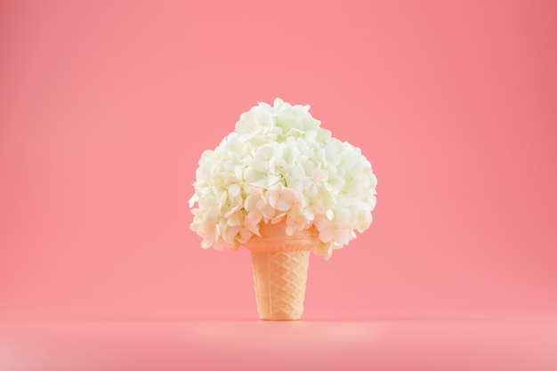 A bouquet of white flowers in an ice cream cone on pink.