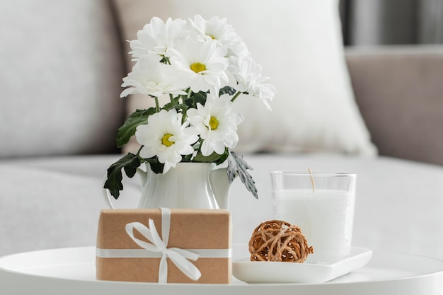 Bouquet of white flowers in a vase with wrapped gift