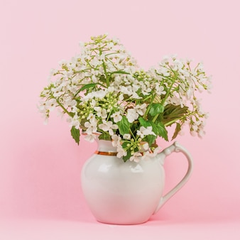 Bouquet of white forest flowers in a white jug on a pink background close-up
