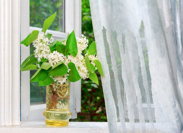 Bouquet of white lilac flowers on a white windowsill in a village house