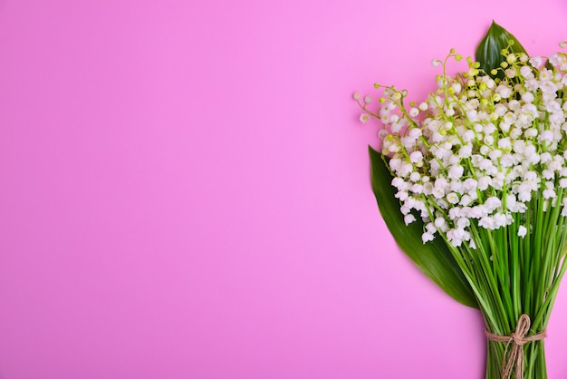 Bouquet of white lilies of the valley on a pink surface