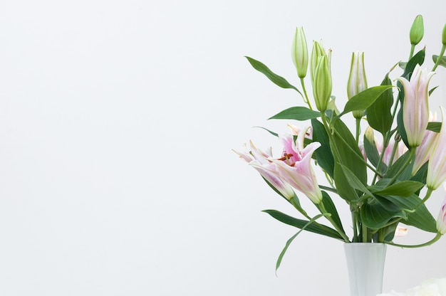 Bouquet of white lilies in a white vase on white background