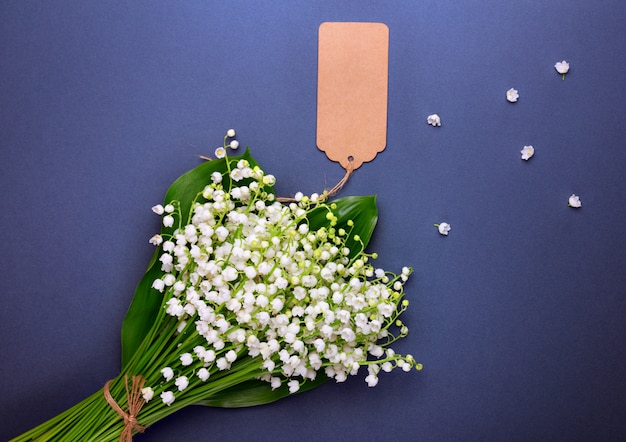 Bouquet of white lily-of-the-valley with an empty paper tag