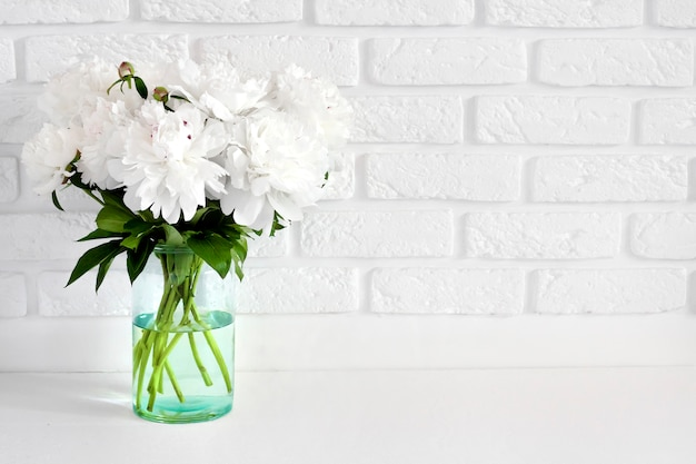 Bouquet of white peonies in a glass vase on a white break wall