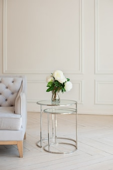 Bouquet of white peonies stands in vase on table near gray sofa in white living room.