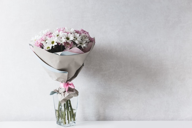 Bouquet of white and pink chrysanthemums in glass vase on table.