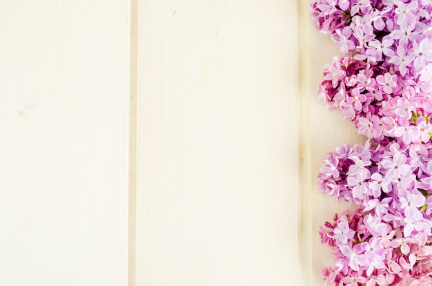 Bouquet of white and purple lilac branches on wooden table background