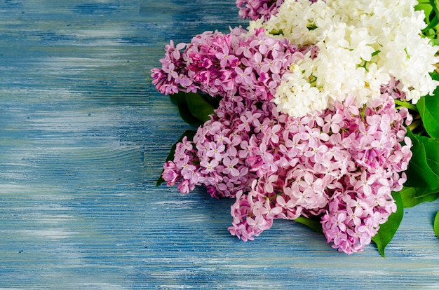 Bouquet of white and purple lilac branches on wooden table