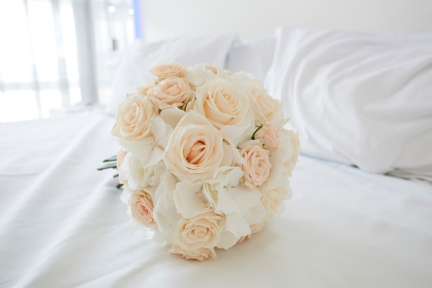 Bouquet of white roses on a bed