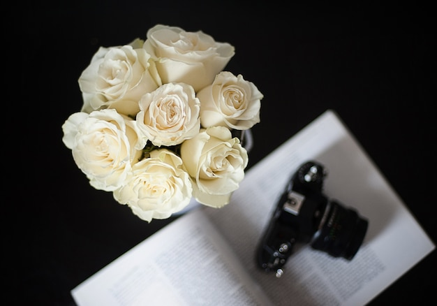 Bouquet of white roses on a black background, focus on flowers
