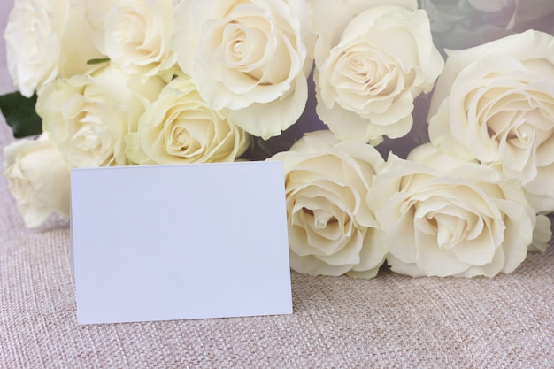 Bouquet of white roses and a blank card